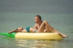 Pares románticos que mienten en cama El hombre y la mujer en la luna de miel, nadada en la piña formaron el colchón en el mar Par Fotos de archivo
