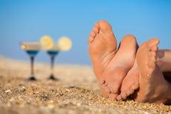 Pares románticos que mienten en una playa Fotos de archivo