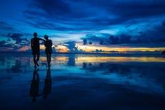 Pares románticos que miran la puesta del sol en la playa Fotografía de archivo libre de regalías
