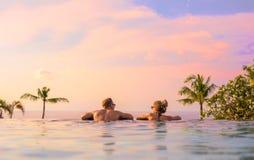 Pares románticos que miran puesta del sol hermosa en piscina de lujo del infinito fotos de archivo libres de regalías