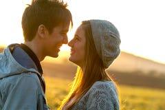 Pares románticos que muestran el afecto en la puesta del sol. Imagenes de archivo