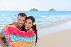 Pares románticos que nadan que bañan la toalla en la playa Fotografía de archivo