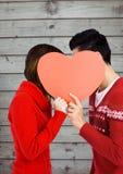 Pares románticos que ocultan su cara detrás del corazón Imágenes de archivo libres de regalías