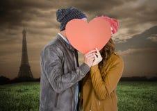 Pares románticos que ocultan su cara detrás del corazón Foto de archivo