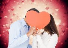 Pares románticos que ocultan su cara detrás del corazón Imagen de archivo libre de regalías