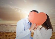 Pares románticos que ocultan su cara detrás del corazón rojo Imagen de archivo libre de regalías