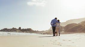 Pares románticos que recorren en la playa fotos de archivo libres de regalías