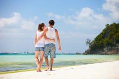 Pares románticos que recorren a lo largo de la playa tropical Fotografía de archivo