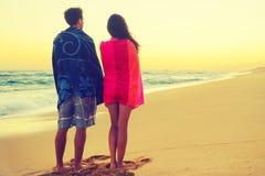 Pares románticos que se bañan con las toallas en puesta del sol de la playa Fotos de archivo