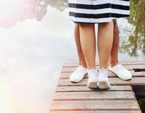 Pares románticos que se besan en el embarcadero cerca del lago en día de verano Fotografía de archivo libre de regalías