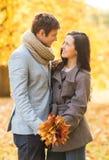 Pares románticos que se besan en el parque del otoño Imagen de archivo libre de regalías
