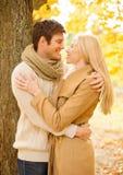 Pares románticos que se besan en el parque del otoño Imagenes de archivo
