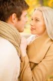 Pares románticos que se besan en el parque del otoño Imagen de archivo