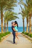 Pares románticos que se besan en la playa con las palmeras Foto de archivo libre de regalías