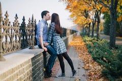Pares románticos que se besan en parque del otoño Foto de archivo