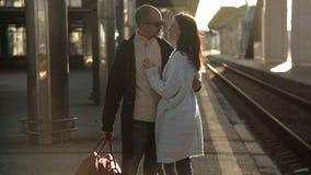 Pares románticos que se besan y que abrazan en la estación de tren antes de la separación almacen de metraje de vídeo