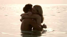 Pares románticos que se colocan en el mar en la puesta del sol almacen de video