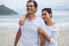 Pares románticos que se colocan en la playa Imagen de archivo libre de regalías