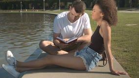 Pares románticos que se relajan con el libro por el agua en parque del verano almacen de video