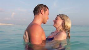 Pares románticos que se relajan en el mar tropical almacen de metraje de vídeo