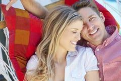 Pares románticos que se relajan en hamaca del jardín junto Imagenes de archivo