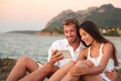 Pares románticos que se relajan en la playa usando la tableta app Imagen de archivo libre de regalías