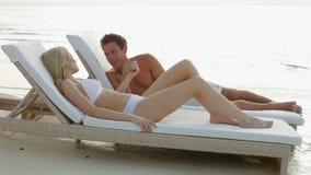 Pares románticos que se relajan en ociosos en la playa almacen de metraje de vídeo