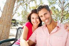 Pares románticos que se sientan en banco de parque junto Imágenes de archivo libres de regalías