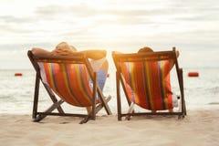 Pares románticos que se sientan en deckchairs en la puesta del sol Imágenes de archivo libres de regalías