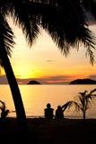 Pares románticos que se sientan en una playa en la puesta del sol Fotos de archivo libres de regalías