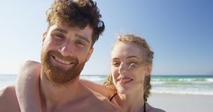 Pares románticos que sonríen en la playa 4k almacen de metraje de vídeo