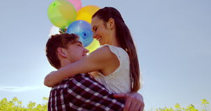 Pares románticos que sostienen los globos coloridos y que se abrazan en campo de la mostaza
