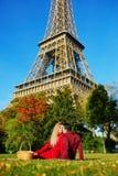 Pares románticos que tienen comida campestre en la hierba cerca de la torre Eiffel fotos de archivo
