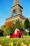 Pares románticos que tienen comida campestre en la hierba cerca de la torre Eiffel foto de archivo
