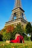 Pares románticos que tienen comida campestre en la hierba cerca de la torre Eiffel foto de archivo libre de regalías