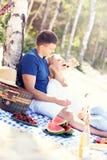 Pares románticos que tienen comida campestre en la playa Fotografía de archivo