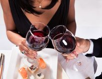 Pares románticos que tuestan el vino rojo Fotografía de archivo