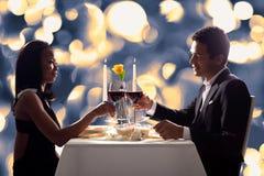 Pares románticos que tuestan el vino rojo Imagenes de archivo
