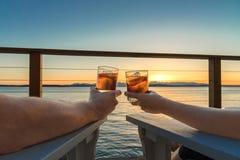 Pares románticos que tuestan la playa de las bebidas en la puesta del sol fotografía de archivo