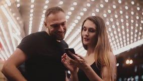Pares románticos sonrientes felices de los turistas que se colocan en sorprender el teatro de Chicago usando mapa del smartphone, metrajes