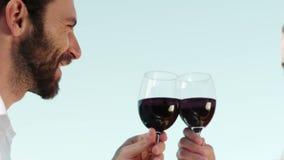 Pares románticos sonrientes que tuestan las copas de vino almacen de video