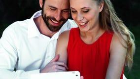Pares románticos sonrientes usando la tableta digital almacen de video