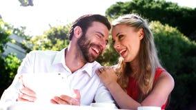 Pares románticos sonrientes usando la tableta digital metrajes