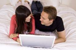 Pares románticos usando la computadora portátil Fotografía de archivo