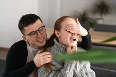 Pares românticos bonitos da surpresa no café O homem cobrir os olhos da sua amiga quando ela que espera uma surpresa imagem de stock royalty free
