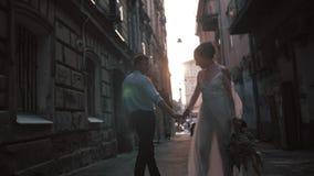 Pares românticos bonitos do casamento de noivo e de noiva no vestido lindo que guarda as mãos ao andar a rua velha de filme