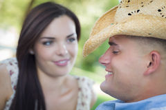 Pares românticos da raça misturada do divertimento no vaqueiro Hat Flirt no parque imagens de stock