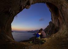 Pares românticos de montanhistas de rocha que olham o por do sol da caverna no cl fotografia de stock