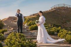 Pares românticos do casamento que estão na escada Fotos de Stock