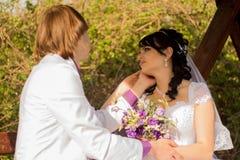 Pares românticos do casamento que sentam-se em um banco no imagens de stock